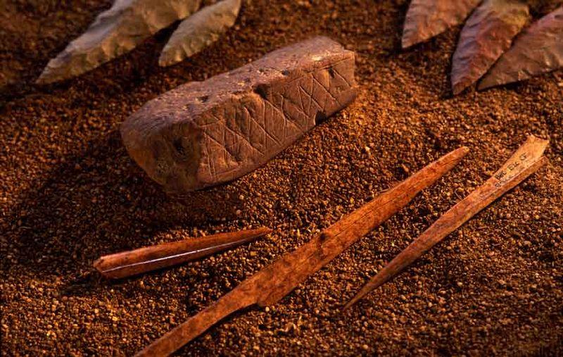 Odkryte wcześniej artefakty z jaskini Blombos datowane na 75 tys. lat: pokryty motywami geometrycznymi kawałek ochry, ostrza kamienne i narzędzia kościane. Źródło: Creative Commons, fot. Ch. Henshilwood